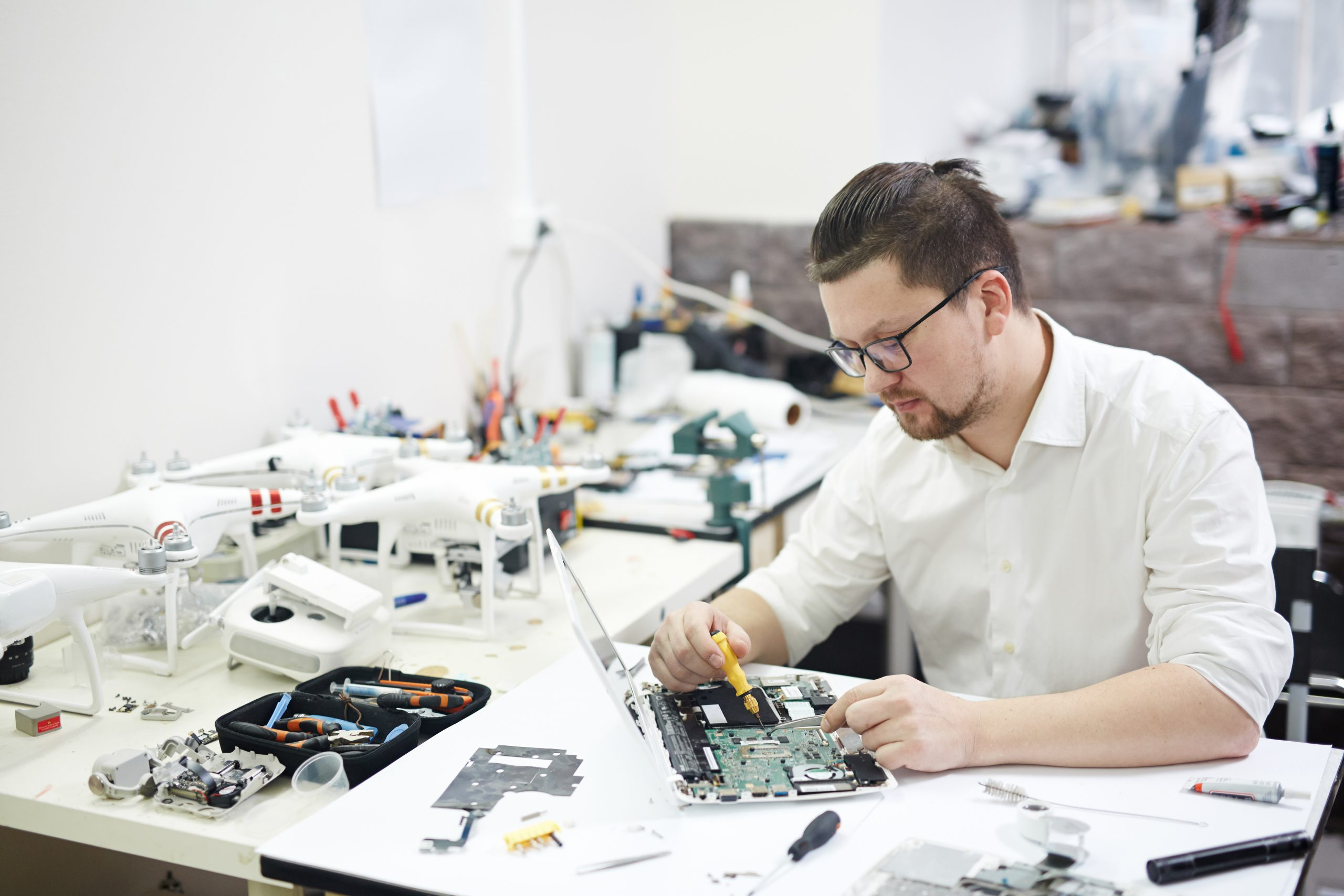 Portrait of modern man wearing glasses busy working with electronics in workshop: disassembling laptop and drones with different tools and electronic devices on table Keywords: